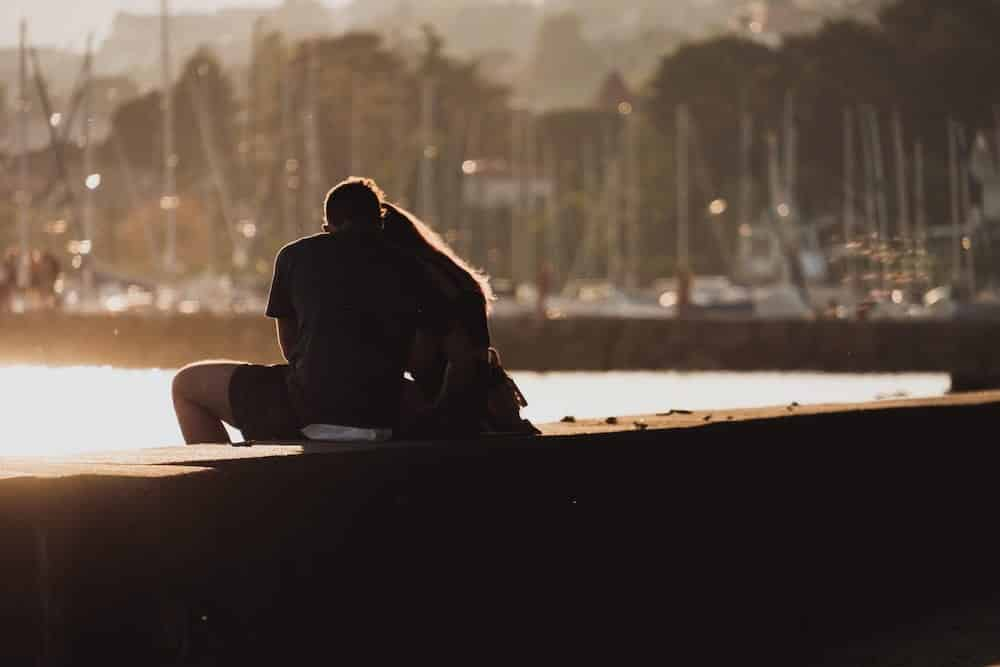 couple sitting on a dock with their arms around each other letting their guard down