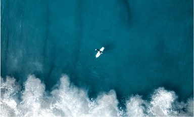 Ariel image of a surfer on white surfboard approaching a crashing wave