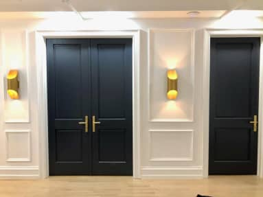 Clarity Therapy office hallway showing navy double doors with brass handles and gold sconces which are illuminated
